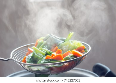 The steam from the vegetable colander in the darkSelective focus. hot food, diet , healthy