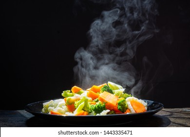 The steam from the vegetables Carrot Broccoli Cauliflower in a black plate  , a steaming. Boiled hot Healthy food on table on black background,hot food and healthy meal concept