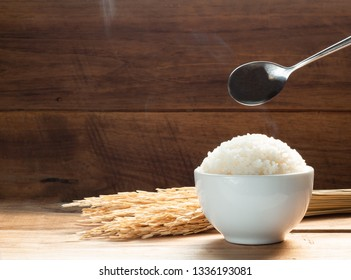 Steam White rice in white ceramic bowl on wood table for healthy meal. Cook concept. Selective focus.