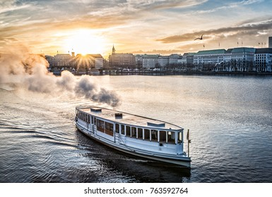 steamboat on Alster Lake in Hamburg, Germany with cityscape in background during sunset