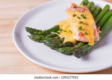Steamed asparagus with baked salmon filet and hollandaise sauce on the top. Delicious healthy meal
