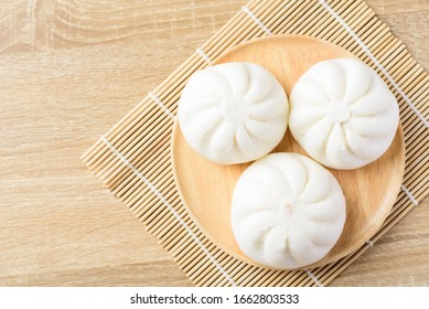 Steamed buns on wooden plate and bamboo sheet ready to eating in the morning, Asian food, Top view