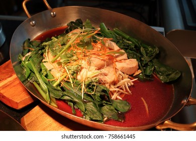 Steamed chicken served in a pan, together with green leafy vegetables