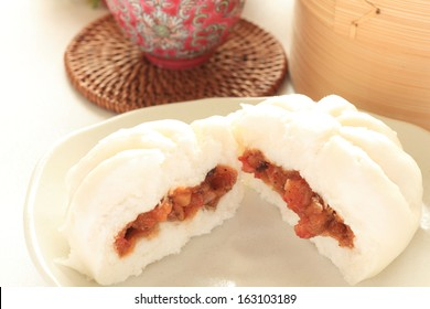 steamed Chinese bun with preserved pork filling on white background