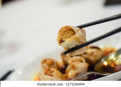 Steamed Chinese dumplings (Shanghai style) on a plate in a sweet soy sauce