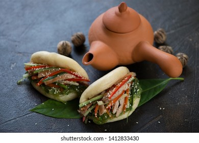 Steamed chinese gua bao and ceramic teapot on a dark brown stone background, studio shot
