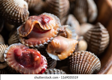 Steamed cockle ( Boiled cockles ) with spicy seafood sauce on wooden background