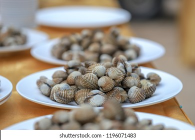 Steamed cockle boiled cockles in Stainless steel tray with wooden table in background,Grilled seafood.