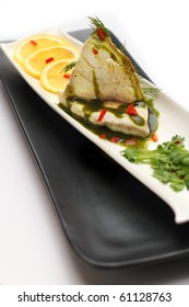 Steamed cod fish topped with special sauce, served with lemon, placed on white and black platter