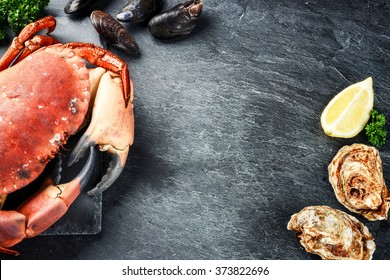 Steamed crab and fresh oysters on dark background. Sea food dinner concept