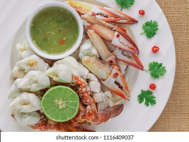 Steamed crab meat prepared for ready to eat with Thai style spicy dipping sauce on white plate in top view flat lay with copy space for background or wallpaper. Delicious homemade seafood concept.
