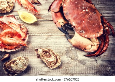 Steamed crab, shrimps and fresh oysters on wooden background. Sea food dinner concept