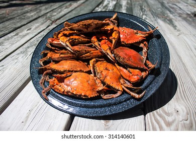 Steamed crabs in a steamer pot lid sitting on weathered wood