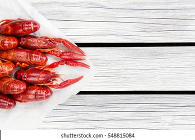 Steamed crawfish. Red boiled crayfish on the white wooden rustic background. Rustic style.