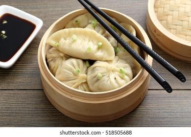 Steamed dumplings in bamboo basket on wooden table background