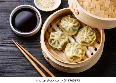 Steamed dumplings Dim Sum in bamboo steamer on black burned wooden background
