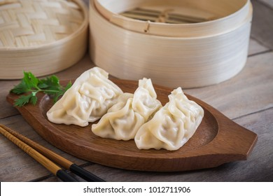 Steamed dumplings on wooden plate