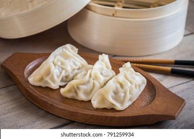 Steamed dumplings on wooden plate