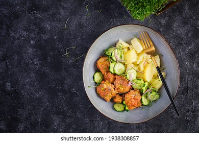 Steamed fish fillet with tomatoes sauce, boiled potatoes and fresh cucumber salad. Diet meal. Lenten food. Top view, above