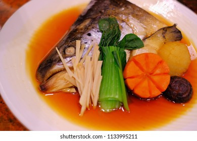 Steamed fish head and vegetables with soy sauce, in warm light. Selective focus.