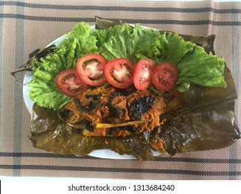 Steamed fish with spicy curry served on banana leaf and salad accessories in top view shot. Delicious famous Indonesian fish food called PEPES IKAN