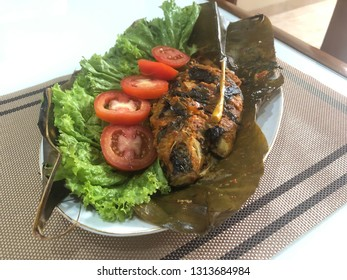 Steamed fish with spicy curry served on banana leaf and salad accessories. Delicious famous Indonesian fish food called PEPES IKAN