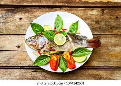 Steamed fish, Tilapia fish steamed with lemon sauce, Thai food, on light wood background textures. low fat food for diet,