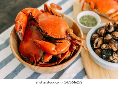 Steamed Giant Mud Crabs in wooden bowl served with Thai spicy seafood sauce and Grilled Laevistrombus Canarium in shell.