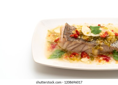 Steamed Grouper Fish Fillet with Chili Lime Sauce in lime dressing isolated on white background