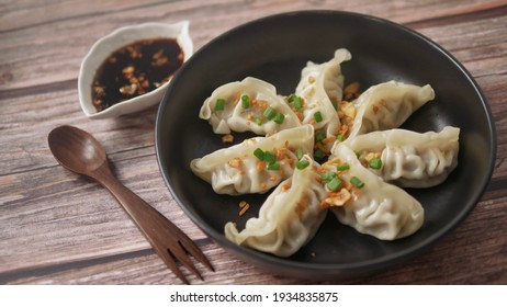 Steamed Gyoza or dumpling stuffed ground pork dipping with garlic soy sauce, famous Chinese appetiser.