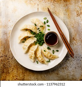 Steamed Gyoza dumplings on plate and sauce on metal background