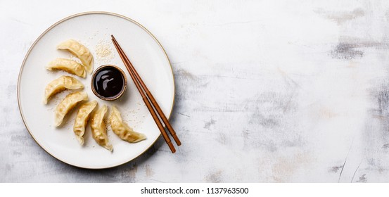 Steamed Gyoza dumplings on plate, sesame and sauce on white wooden background copy space