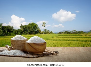 Steamed Jasmine rice in wooden bowl with the chopsticks on the wooden table with the rice plantation