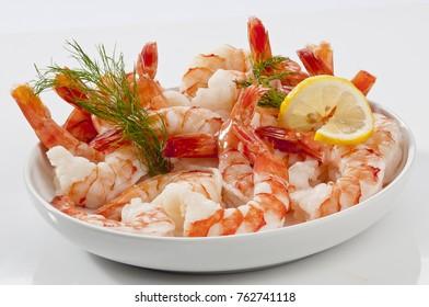 Steamed Jumbo headless shrimps with deli leaves and Lemon on white plate on white background
