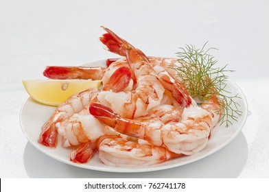 Steamed Jumbo headless shrimps with deli leaves and Lemon on white plate on white background