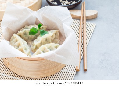 Steamed Korean dumplings Mandu with chicken meat and vegetables in a bamboo steamer, horizontal, copy space