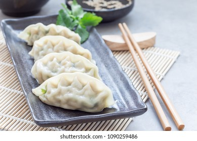 Steamed Korean dumplings Mandu with chicken meat and vegetables on a black plate, horizontal, copy space