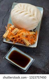 Steamed korean pigodi bun with salad, vertical shot on a grey stone background