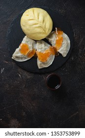 Steamed korean pigodi with potstickers, flatlay on a dark brown stone background, vertical shot with copyspace