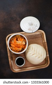 Steamed korean traditional tin-pun or pigodi on a wooden serving tray. Above view on a dark brown metal background