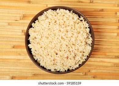 Steamed long rice in a brown bowl.