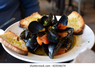 Steamed mussels on a white bowl on a table