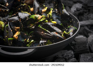 Steamed Mussels with vegetables in a black frying pan on the coals