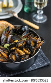 Steamed mussels in white wine sauce in a black pot on the table.