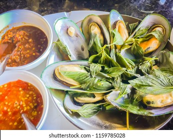 Steamed New Zealand mussels with thai herb in the seafood restaurant. New Zealand green-lipped mussel (Perna canaliculus), also known as the New Zealand mussel, the greenshell mussel, kuku, and kutai