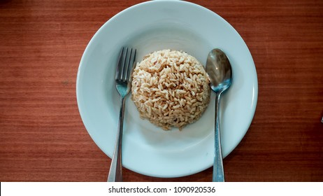 steamed organic brown rice in the white plate with fork and spoon on the wooden table.