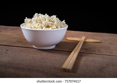 Steamed organic brown rice in the white bowl with wooden chopsticks on wooden table background