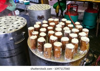 Steamed palm sugar rice cake in bamboo or Putu Bamboo being prepared at street stall during Ramadan buka puasa bazaar or iftar