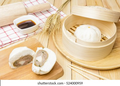 Steamed pork buns (chinese dim sum) in bamboo basket, serve with chopsticks and napkin on wooden background, Closed up