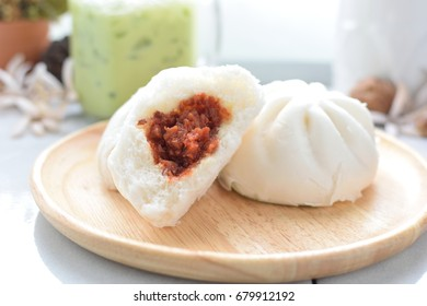 Steamed pork buns  on wood  plate and white table.